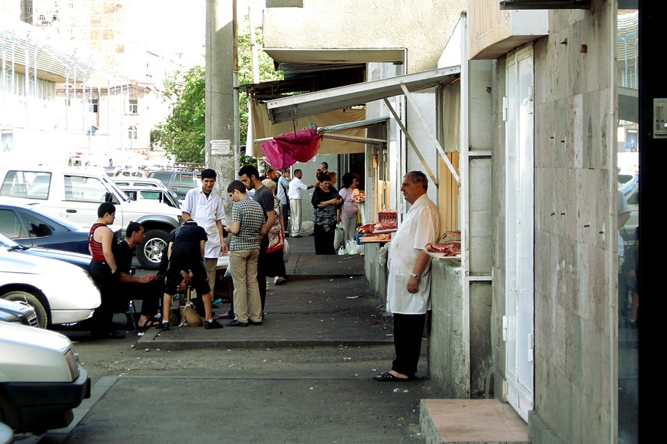 Butcher standing in front of his shop