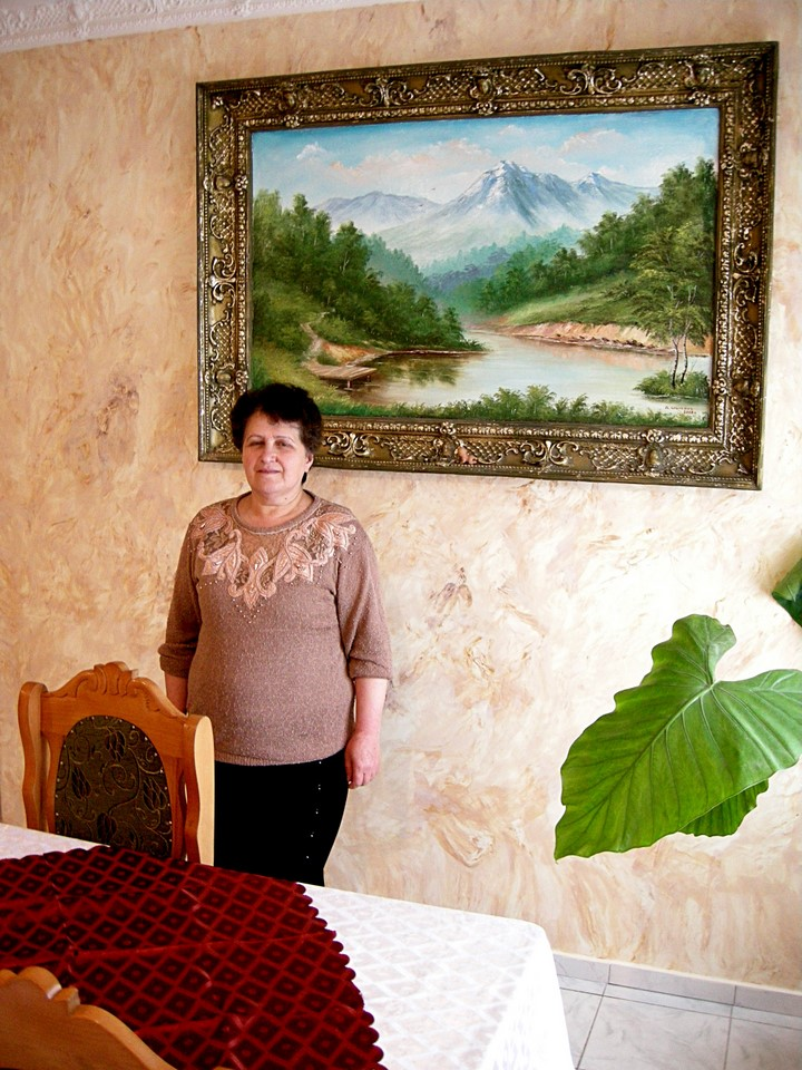 A lady from the hotel posing in front of a landscape painting