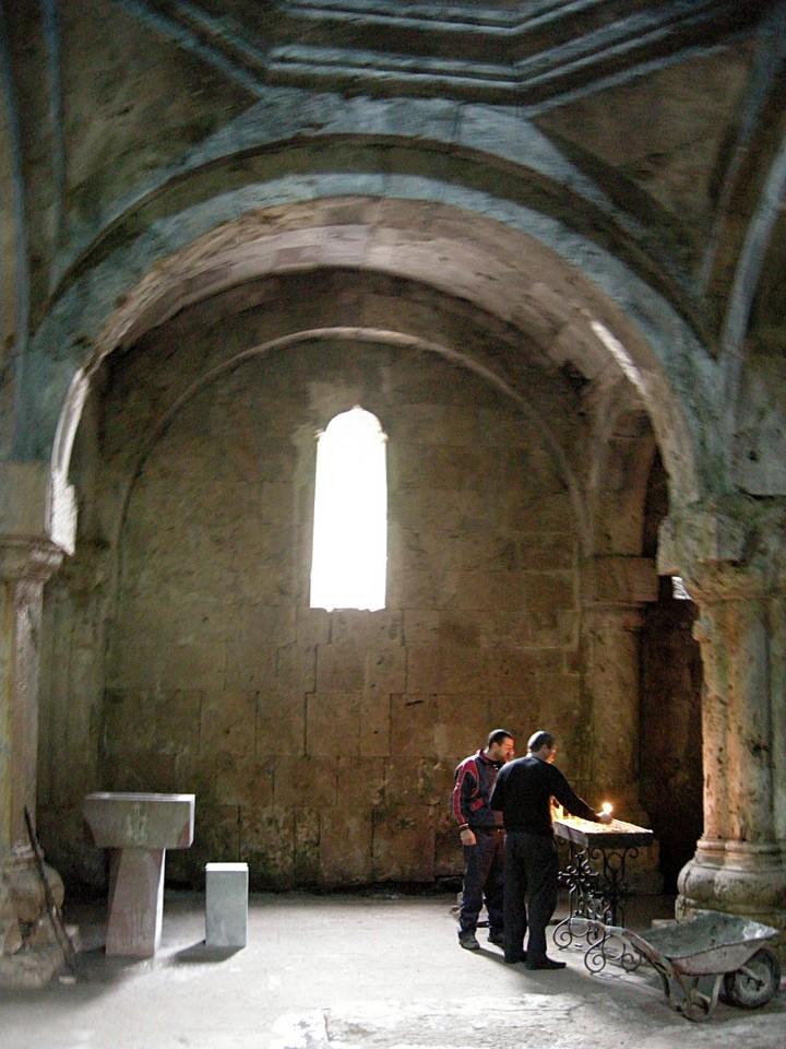 Hommes s'allumant chandelles dans le gavit (narthex) de l'église