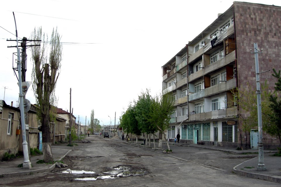 A road in bad condition and an apartment building